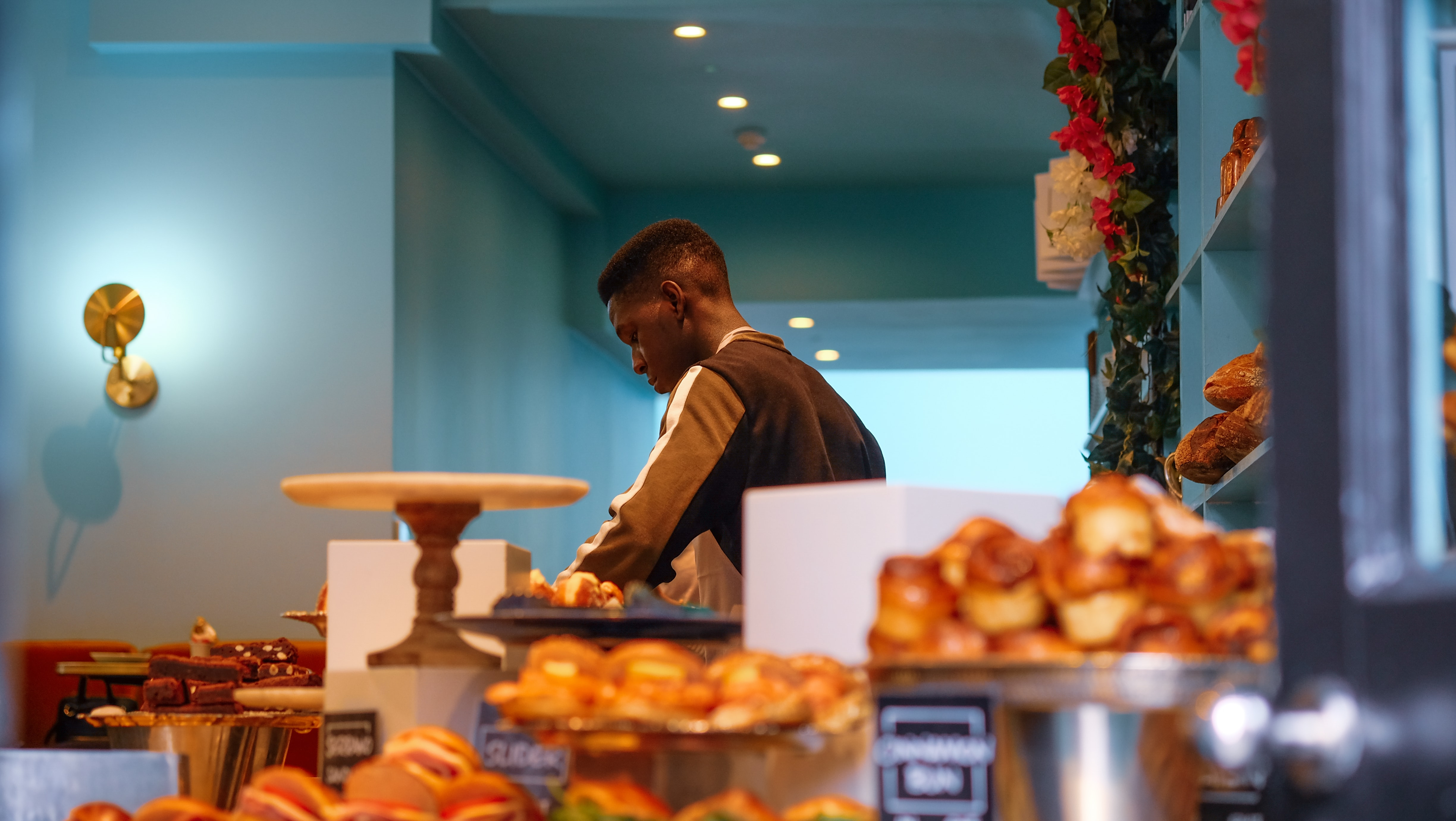 man standing near pastry dishes
