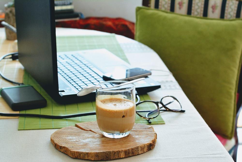 half full half empty drink in clear drinking glass on table beside laptop