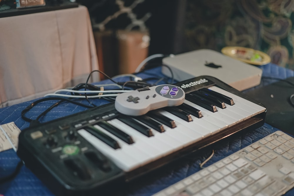 white and black electronic keyboard on blue table