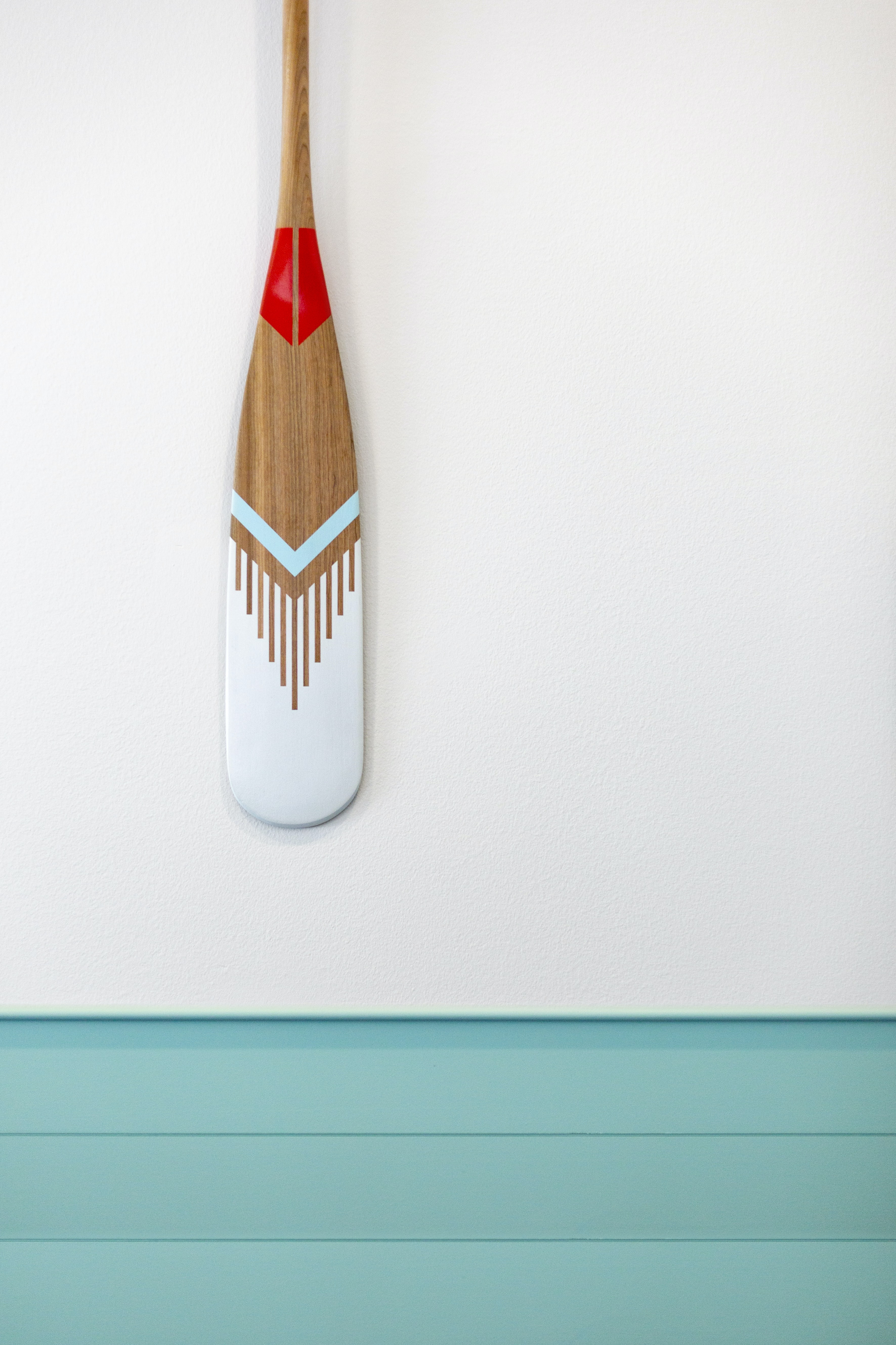 brown, teal, and gray wooden paddle on gray wall