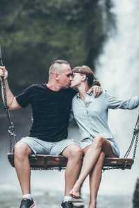 man and woman kissing while riding on swing bench