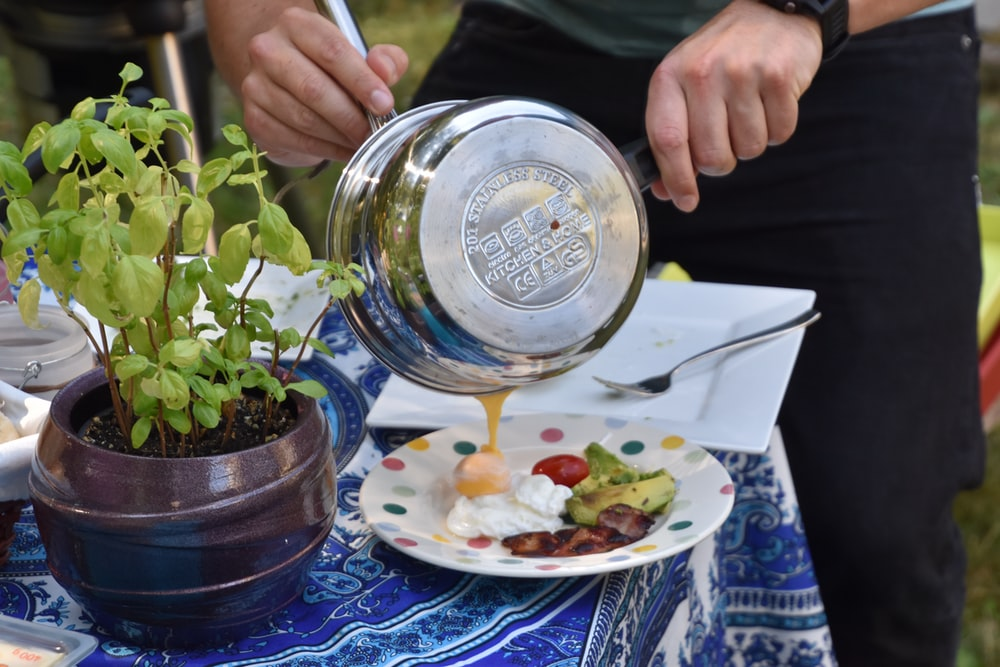person holding pot pouring sauce on plate