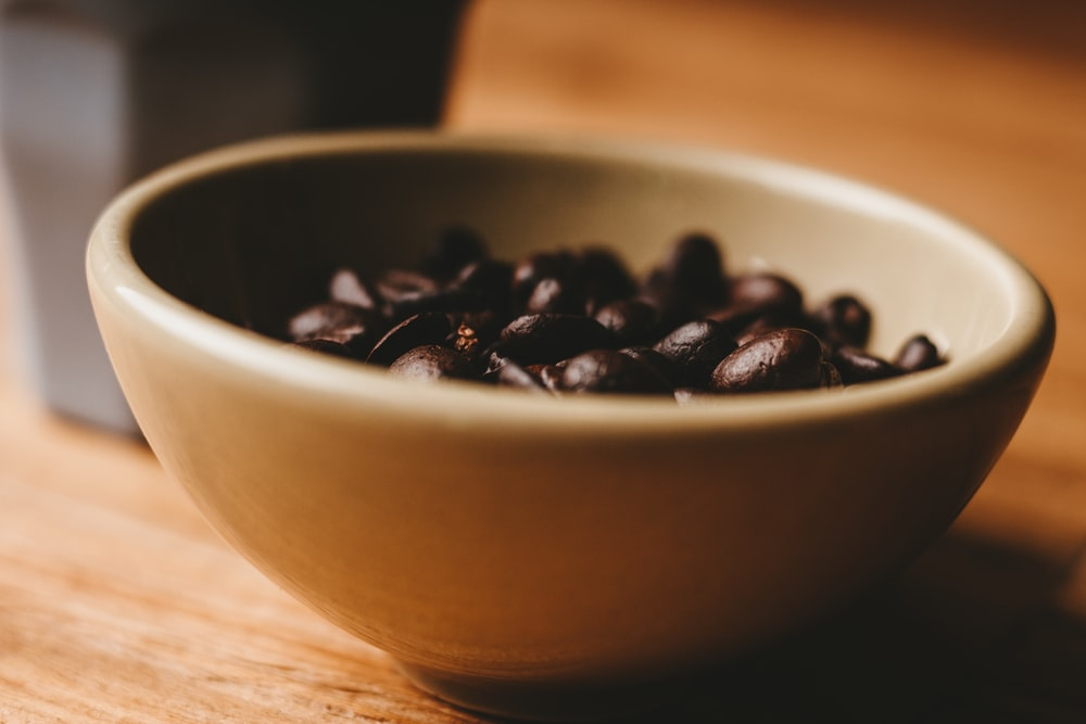 selective photo of coffee beans in white ceramic bowl