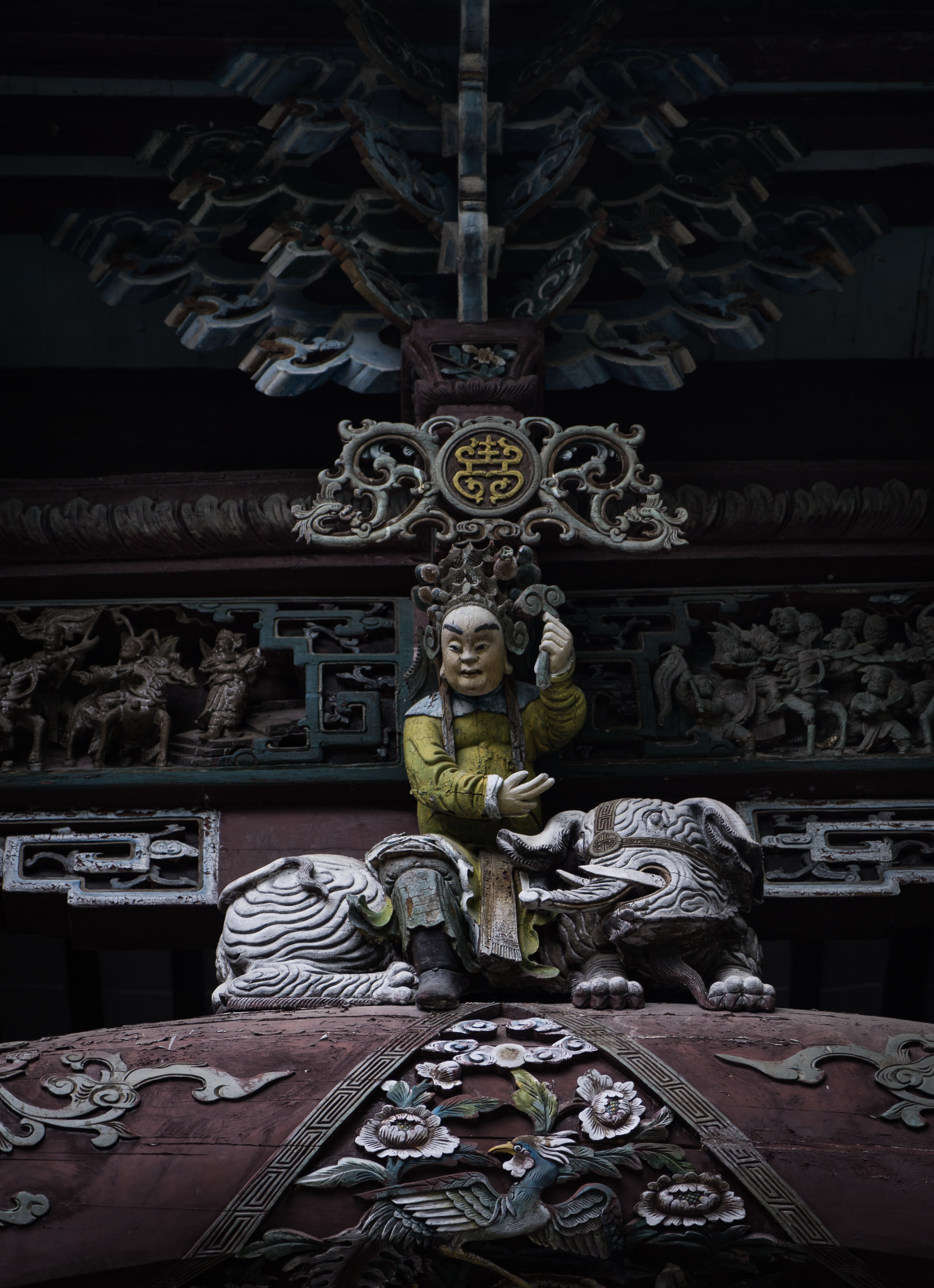 male deity sitting on top of mythical creature statue