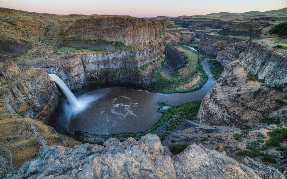 bird eye view photography of waterfalls between cliffs