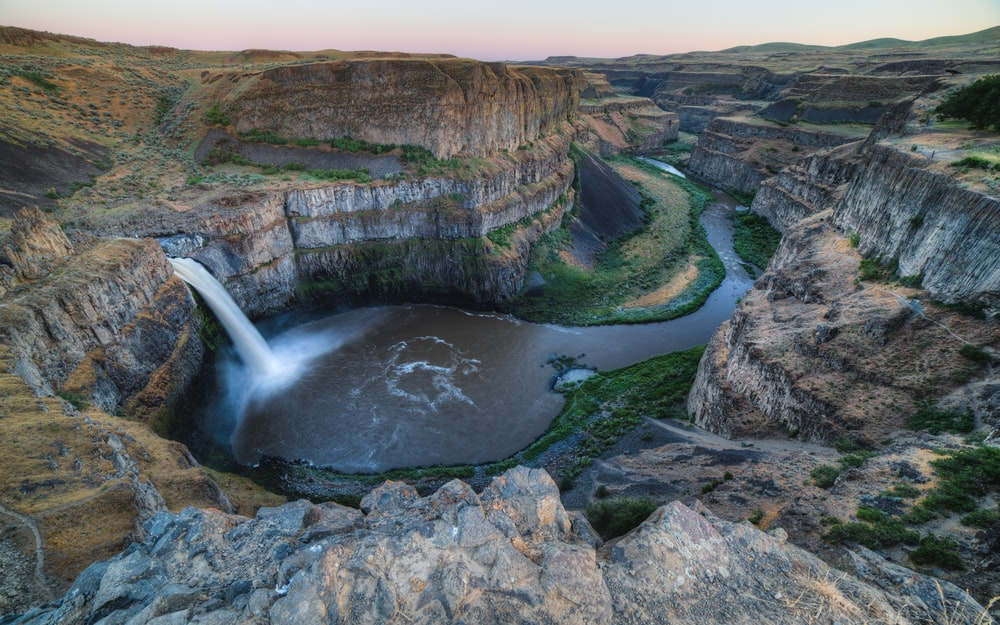 bird eye view photography of waterfalls between cliffs