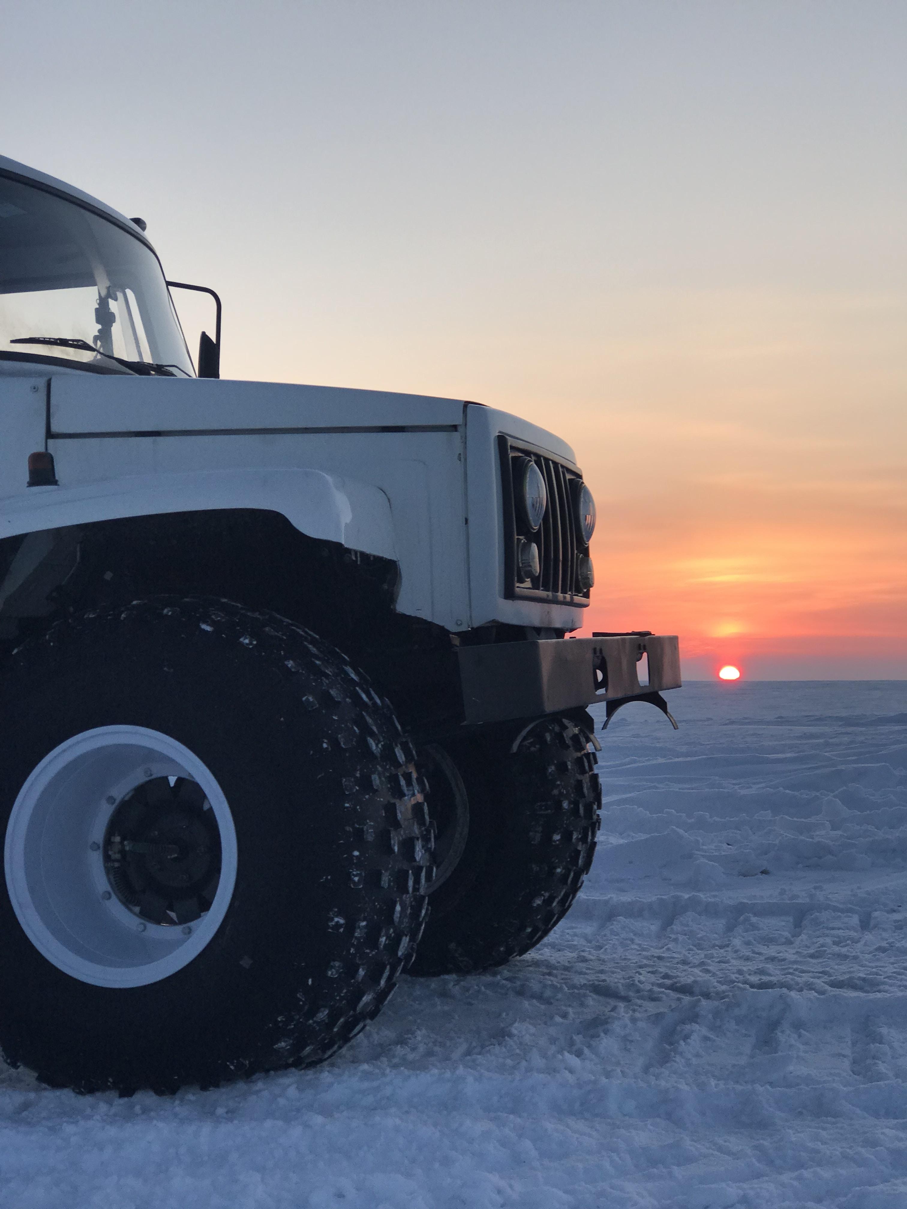 white vehicle parked on seashore with background of sunset