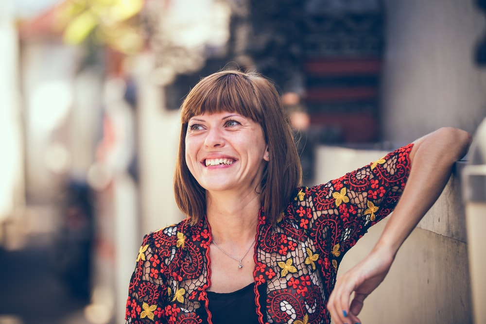 woman in floral-themed cardigan leaning on fence in bokeh photography