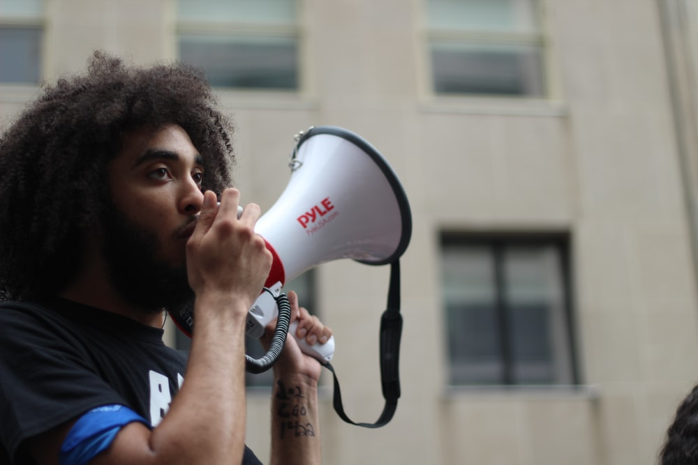 selective focus photography of man holding loudspeaker beside building