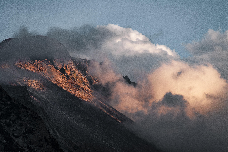 clouds enveloping brown rockhill during daytime