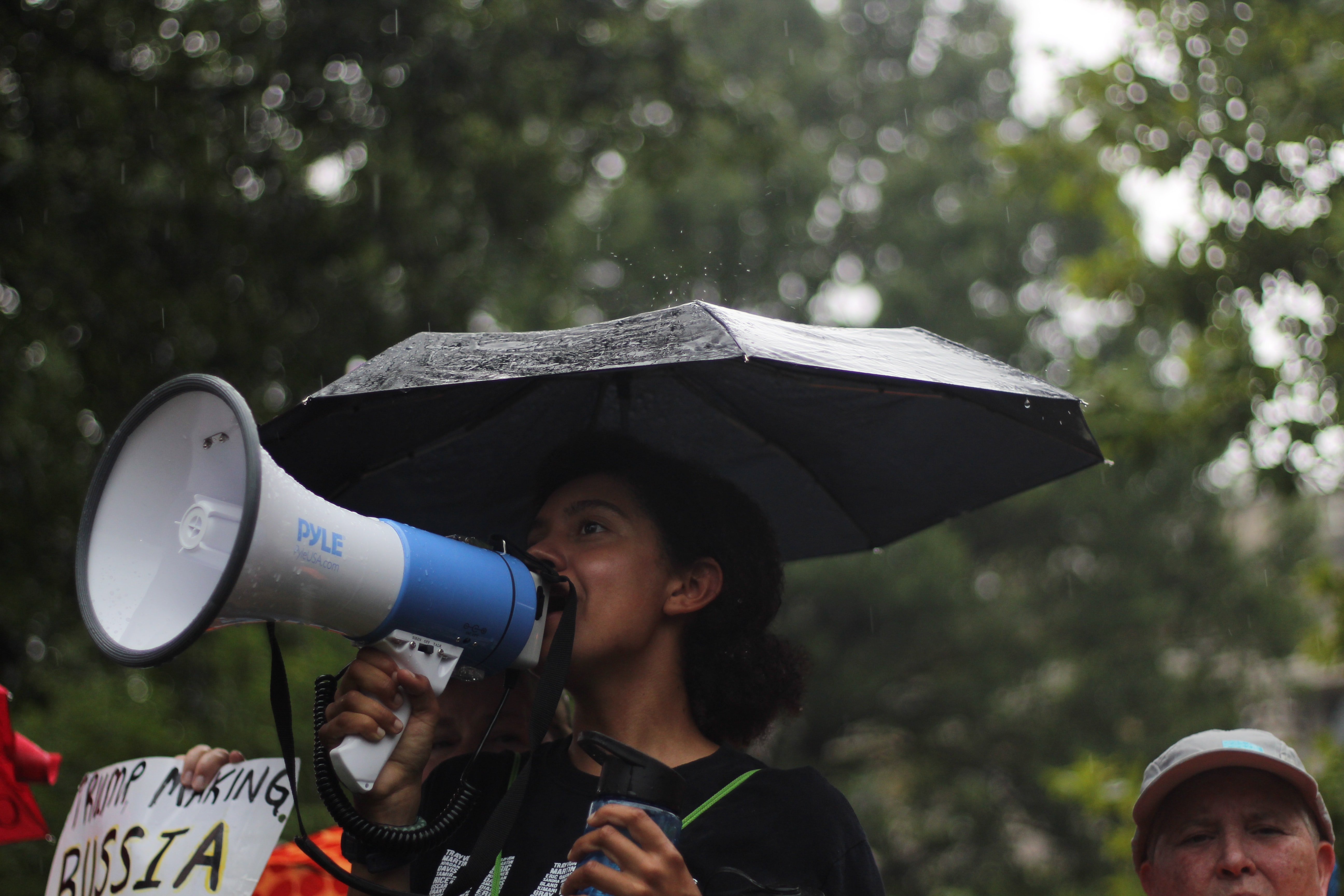 woman standing holding umbrella and white megaphone during daytime