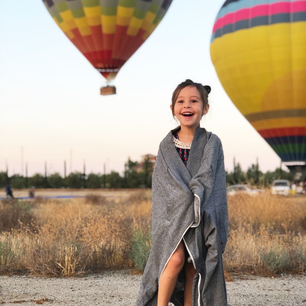 selective focus photography of girl covered by gray scarf with background of hot air balloons