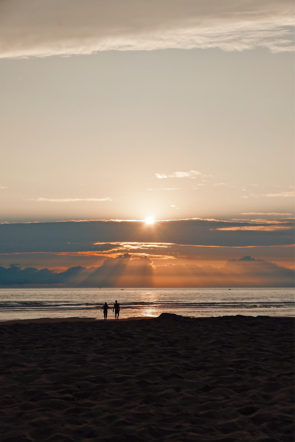 silhouette of man and woman walking on sea shore during sun set