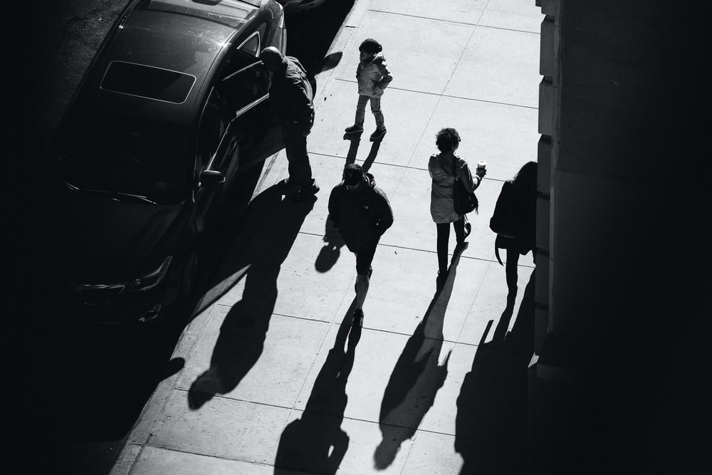 grayscale photo of several people walking on pathway