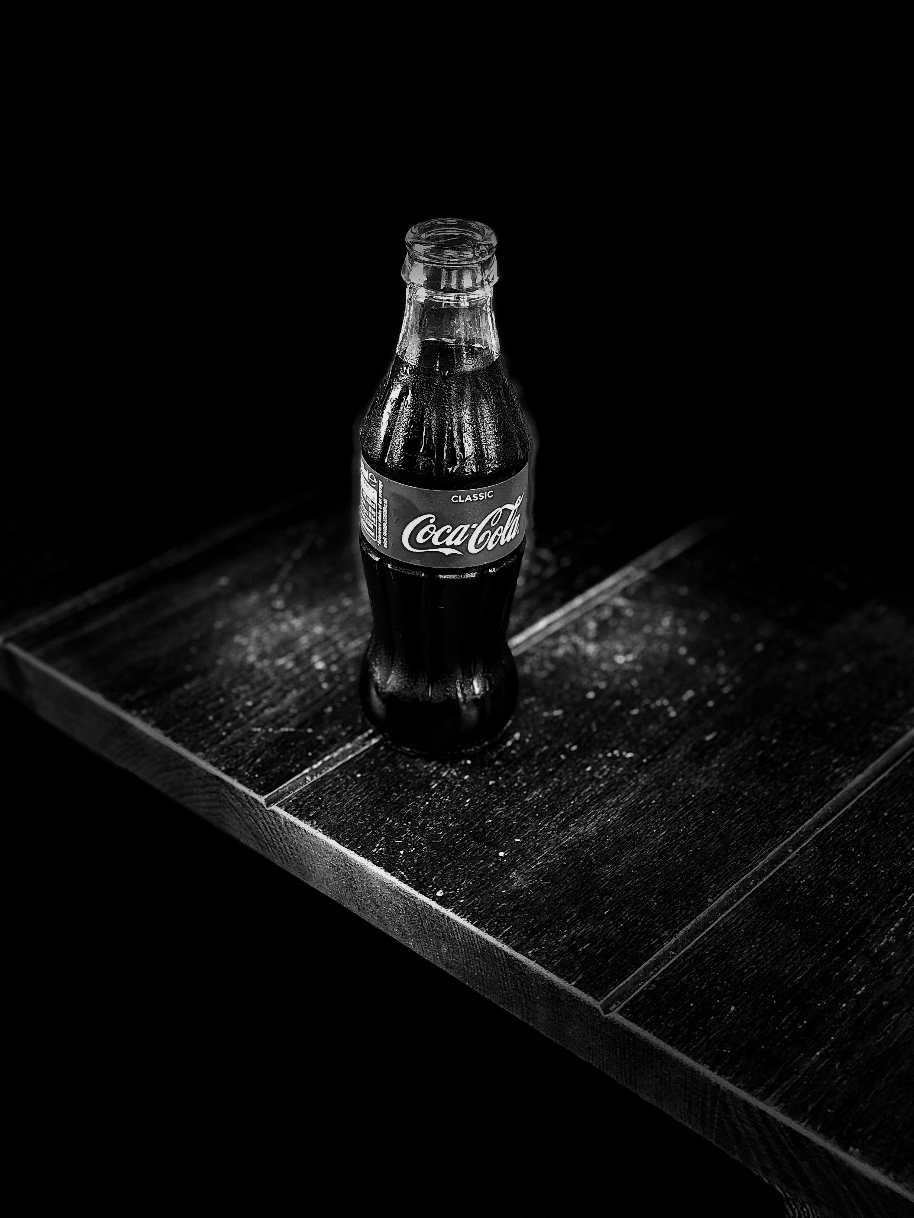 grayscale photography of Coca-Cola bottle on table