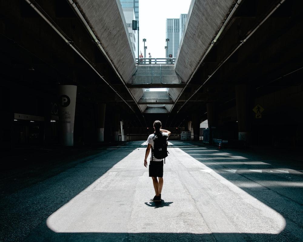 man standing between roads