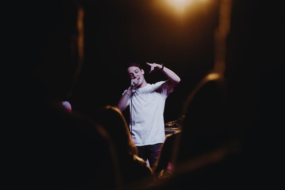 man raising his left hand while singing