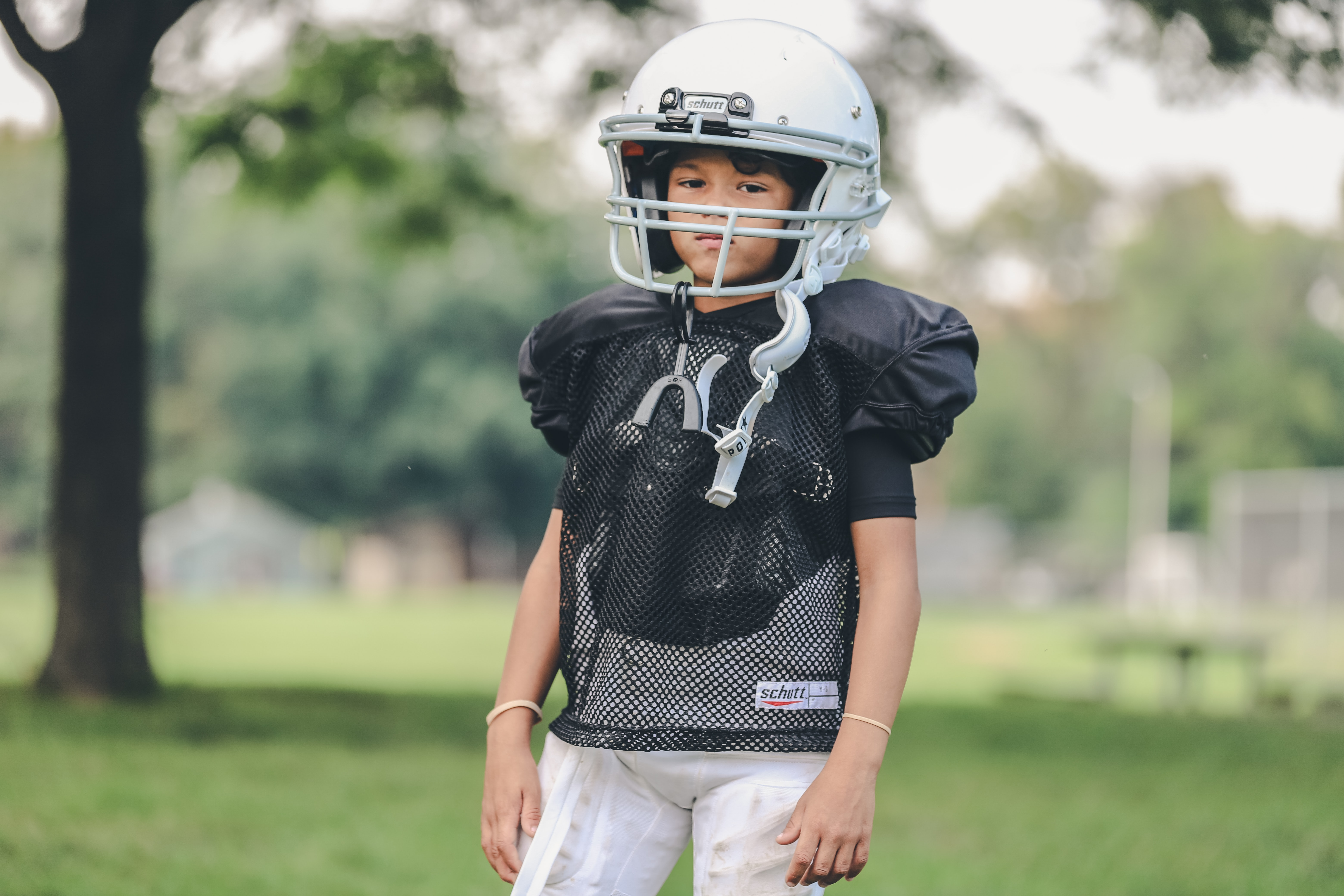 selective focus photography of boy wearing American football gear