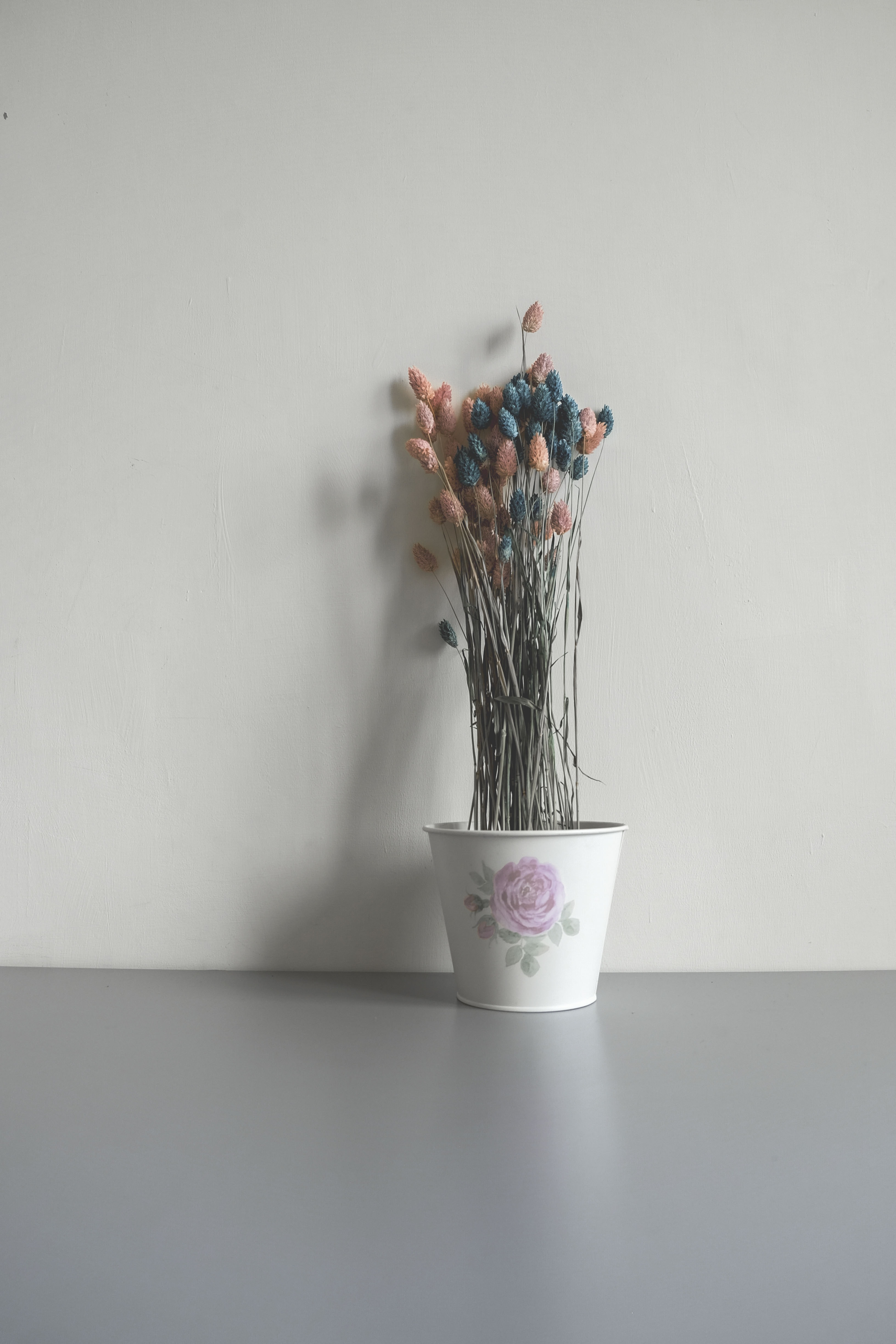 white potted pink and blue artificial flowers near wall