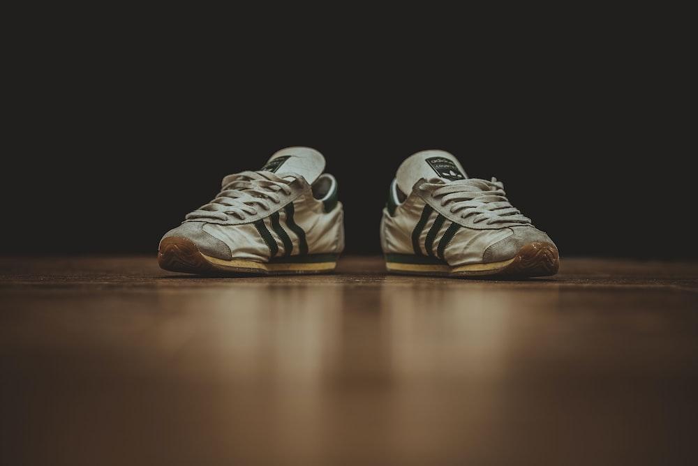 pair of gray adidas low-top sneakers on brown wood