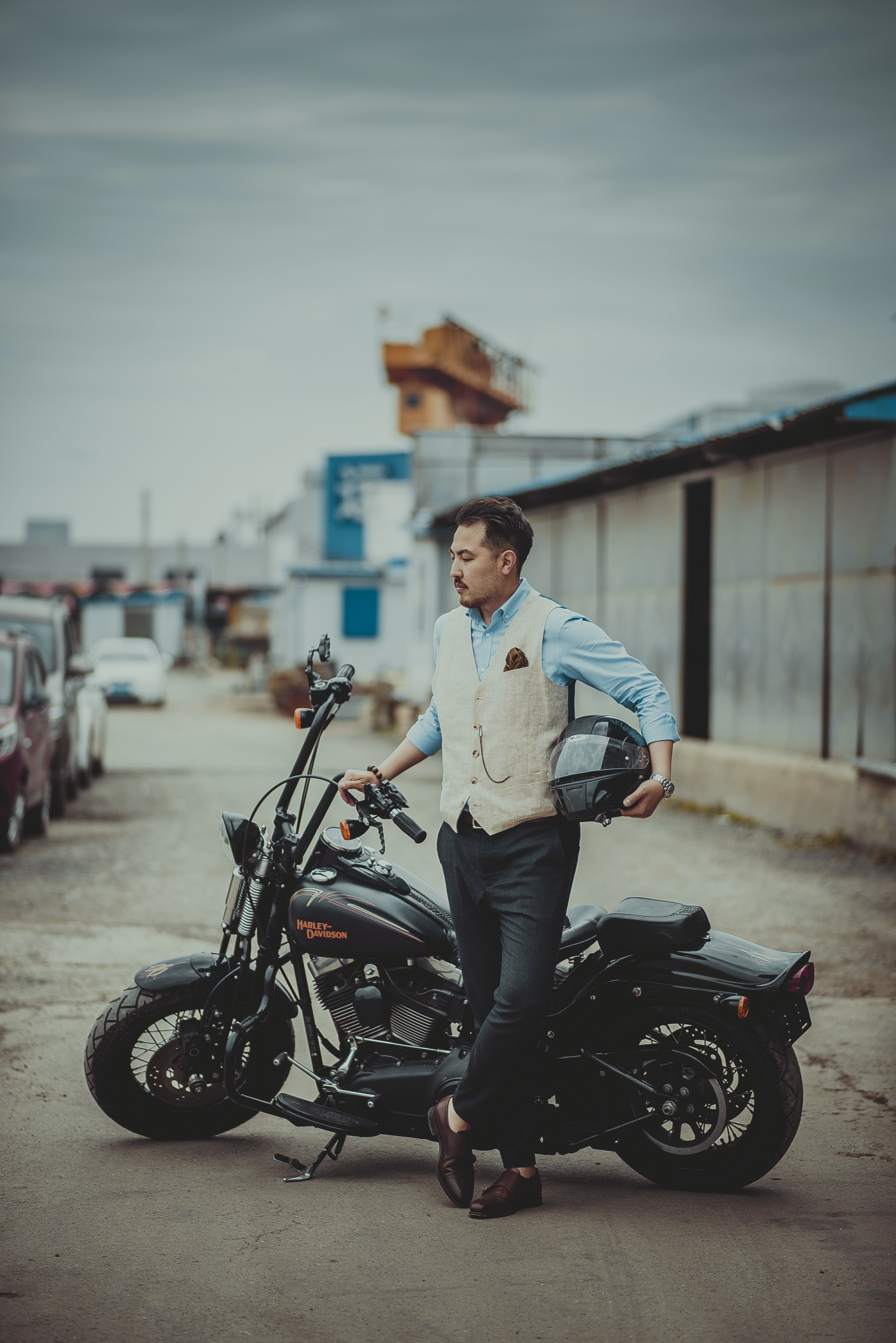 man holding helmet standing beside motorcycle