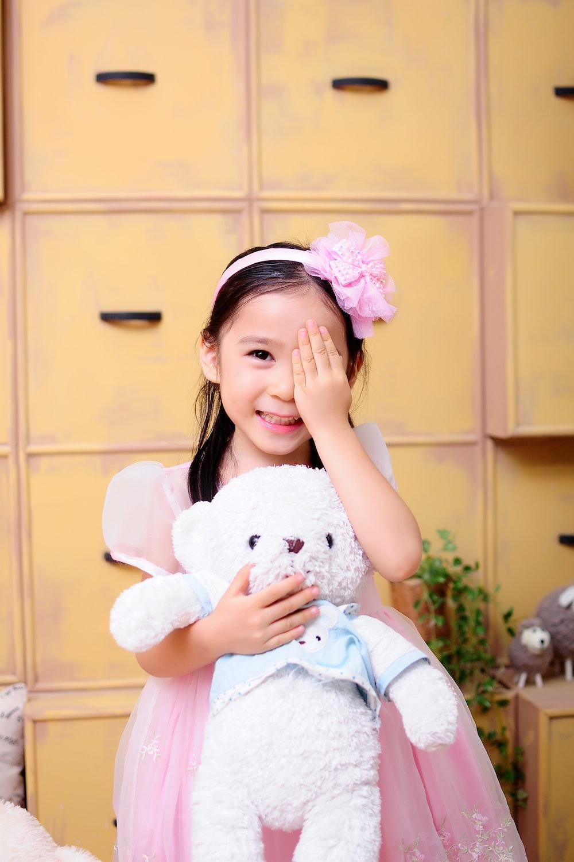 girl hugging brown bear plush toy