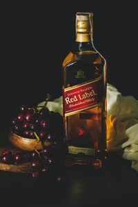 Johnnie Walker red label bottle beside bowl of red grapes