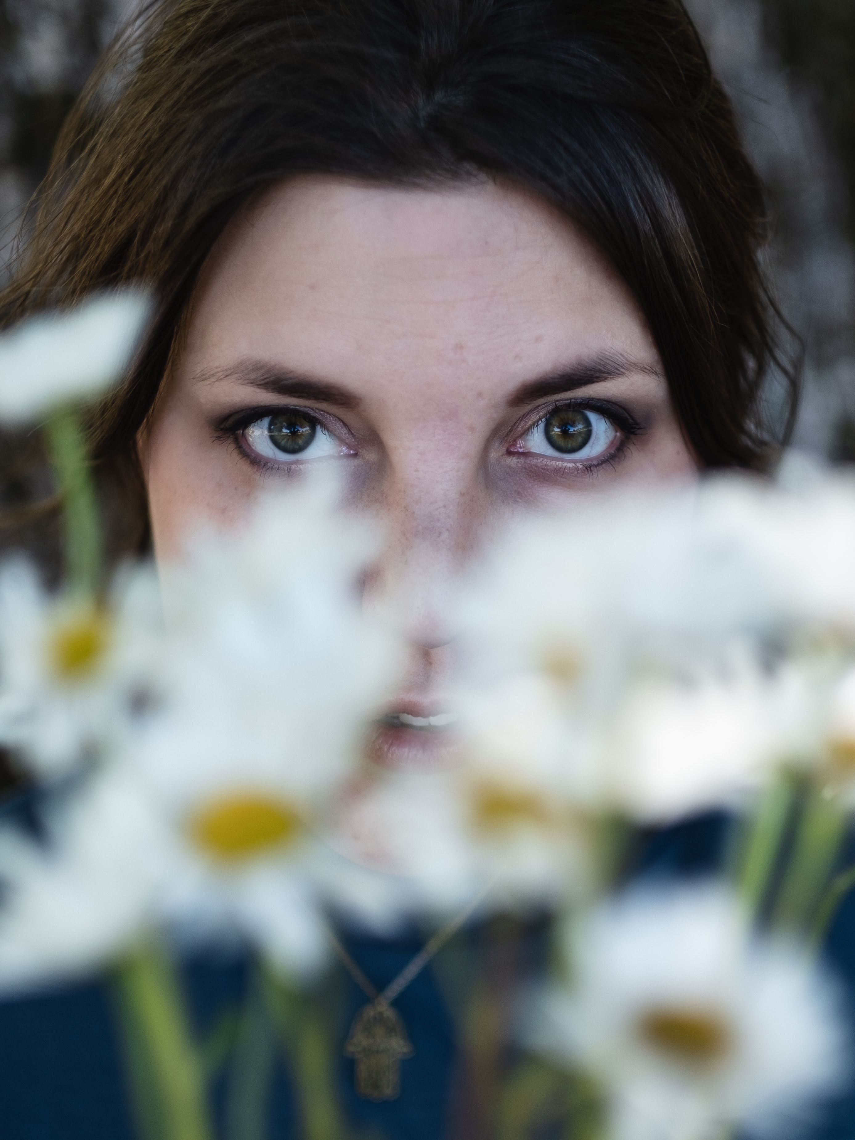 selective focus photography of woman beside daisy flowers