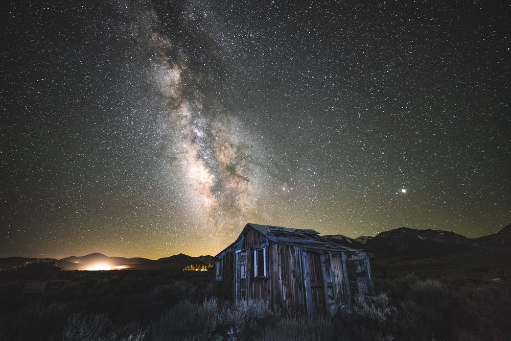 brown and gray wooden house under stars on sky during nighttime