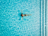 high angle photo woman swimming at body of water