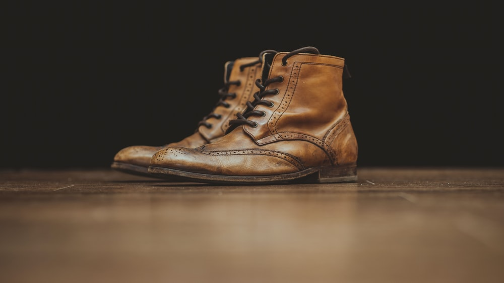 pair of brown leather booties on brown surface