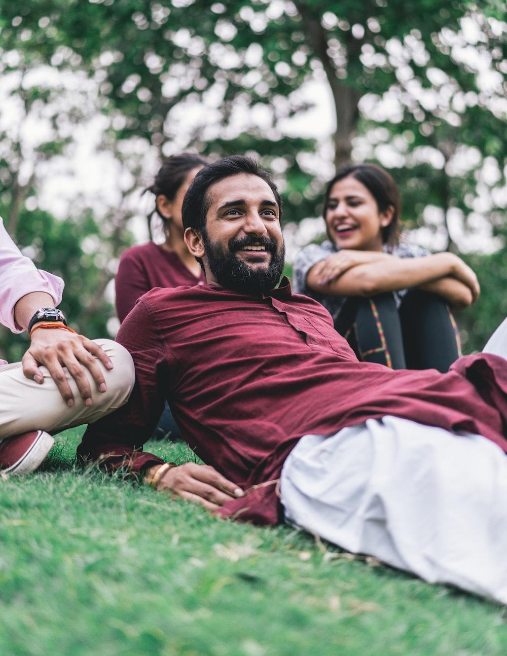 man in maroon dress shirt lying on green grass field
