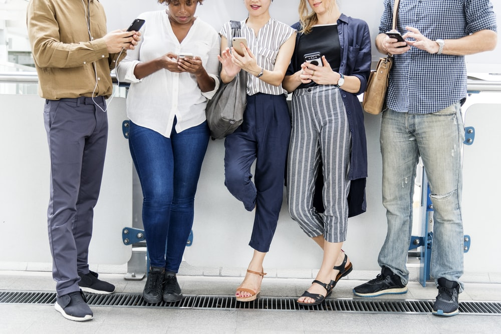 five person standing while using smartphone