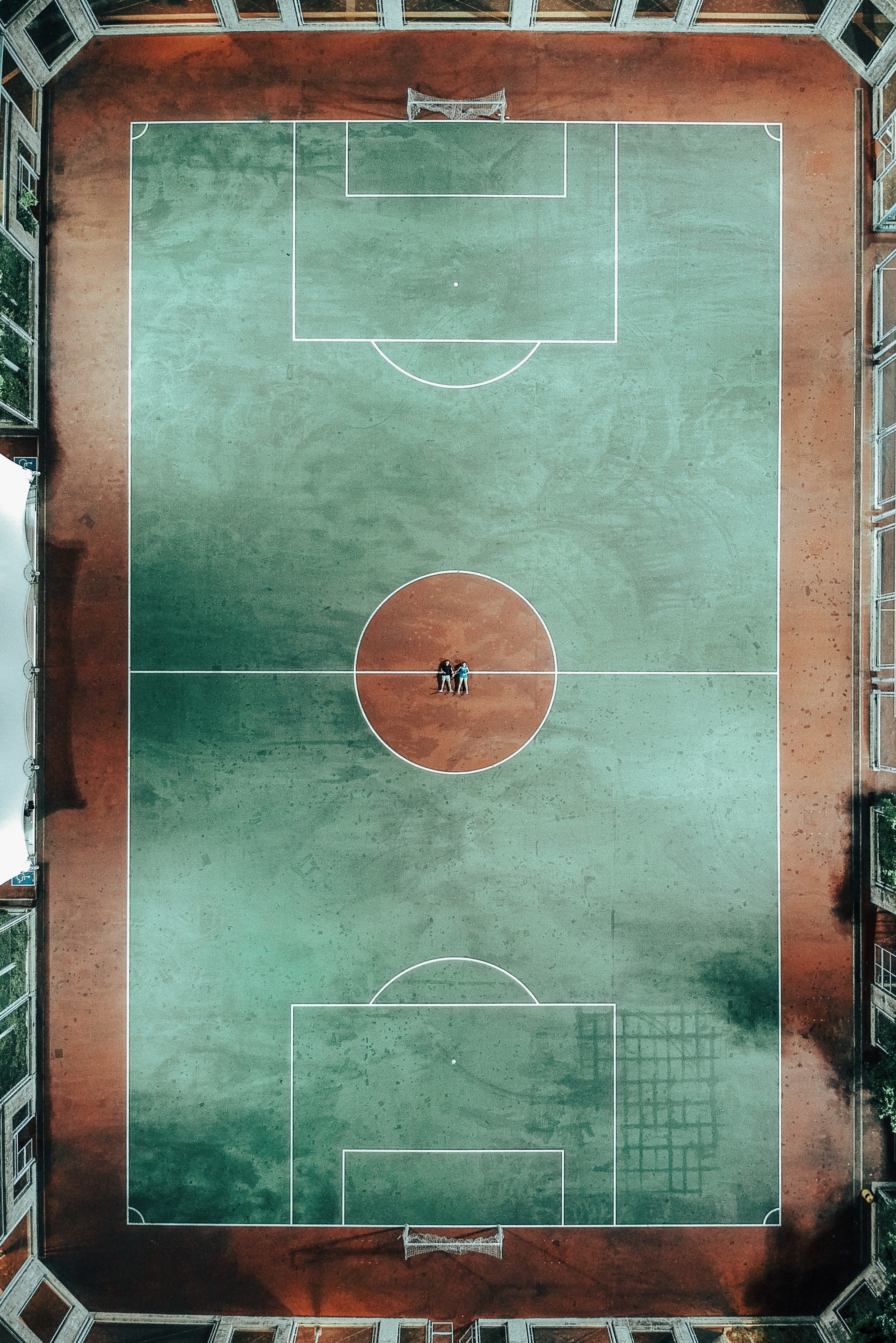 aerial photo of two people lying on green and brown sports court