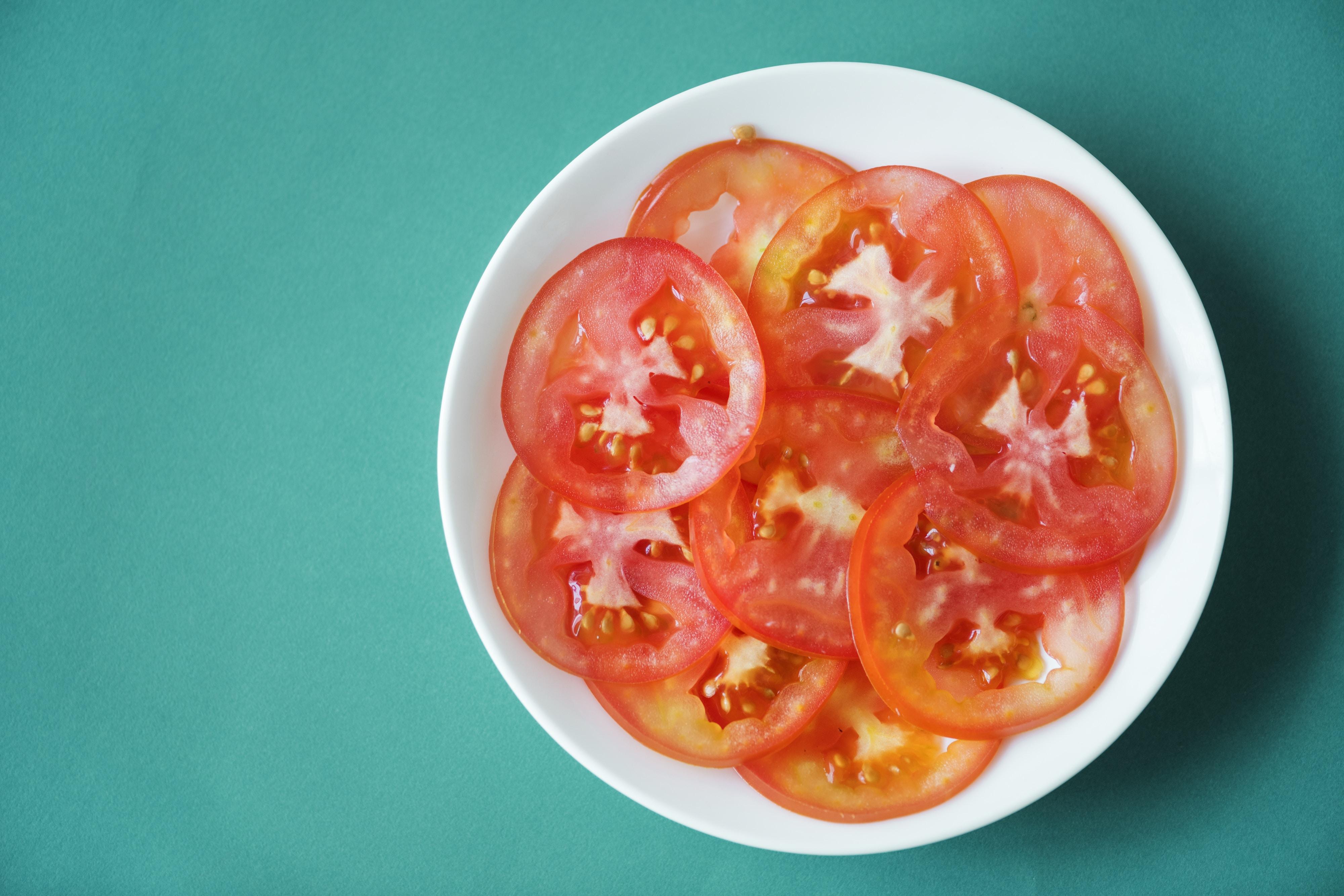 sliced tomatoes on white ceramic bowl
