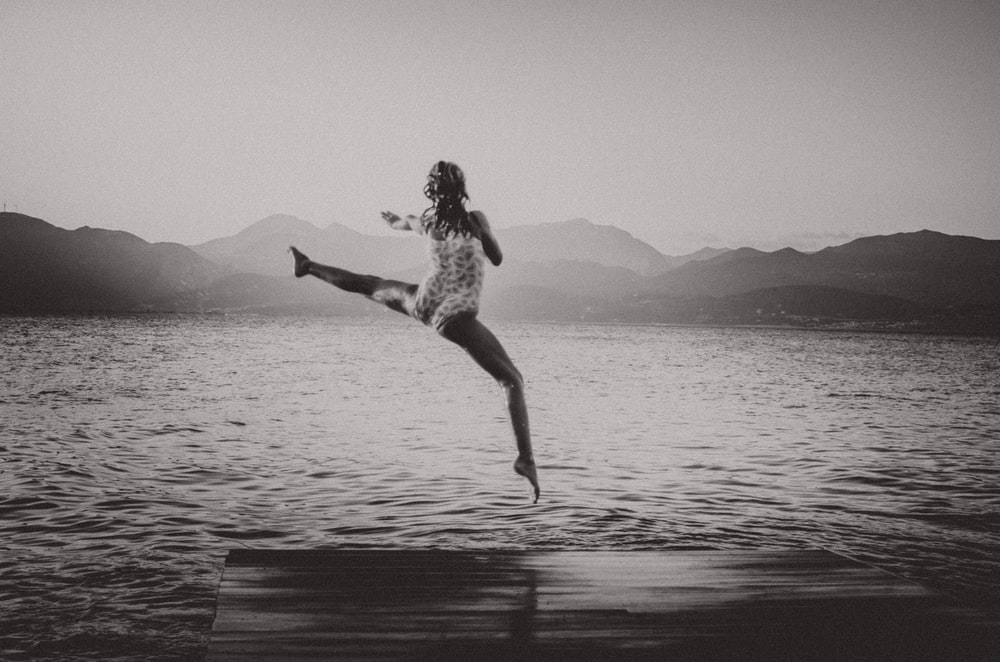 woman jumping on bridge dock