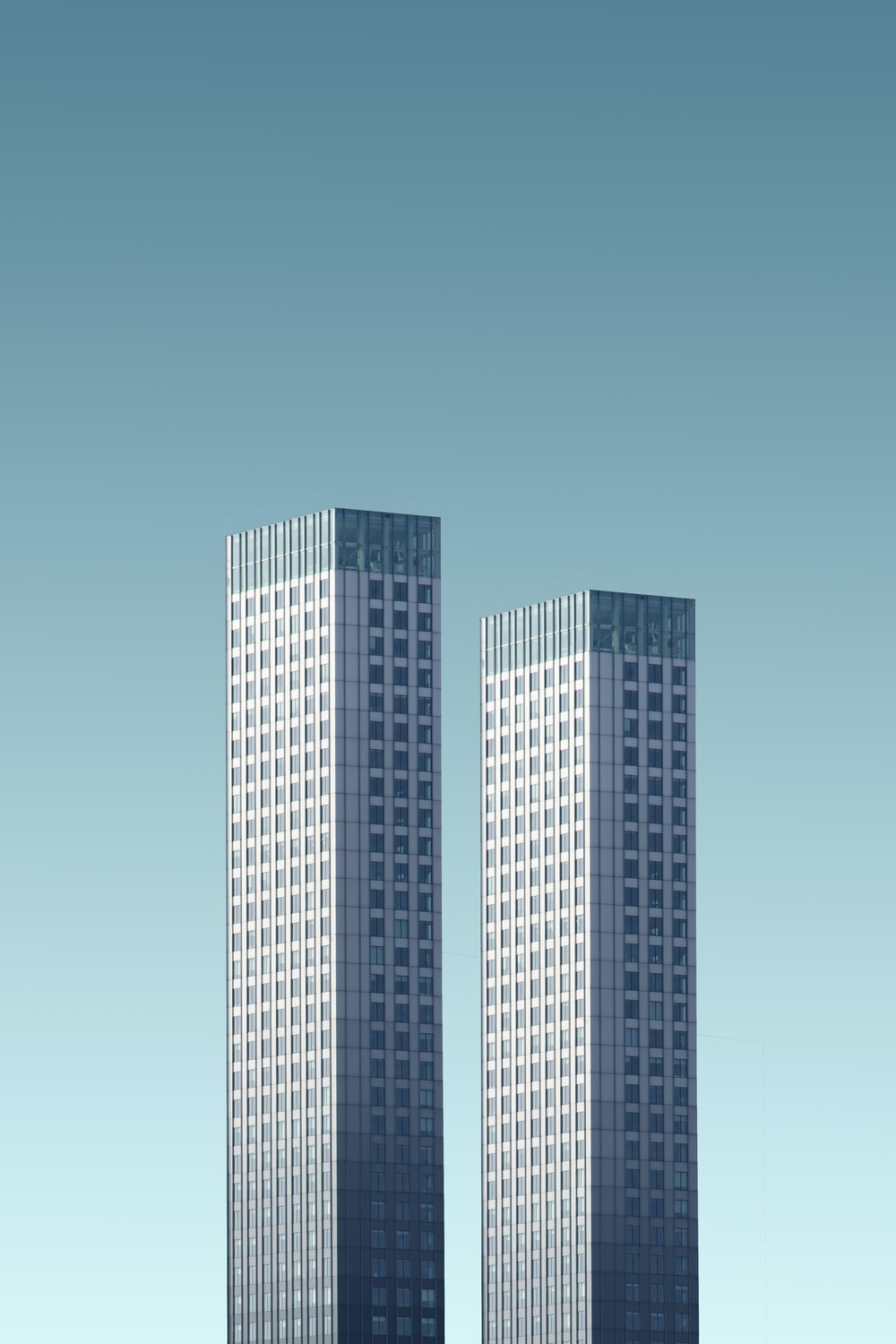 two teal-and-white skyscrapers