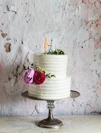 white icing-covered wedding cake on gray cake tray