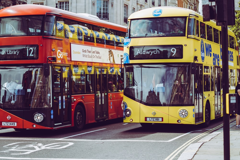 two yellow and red double-decker buses on gray concrete road