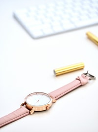 round gold-colored framed analog watch on white surface