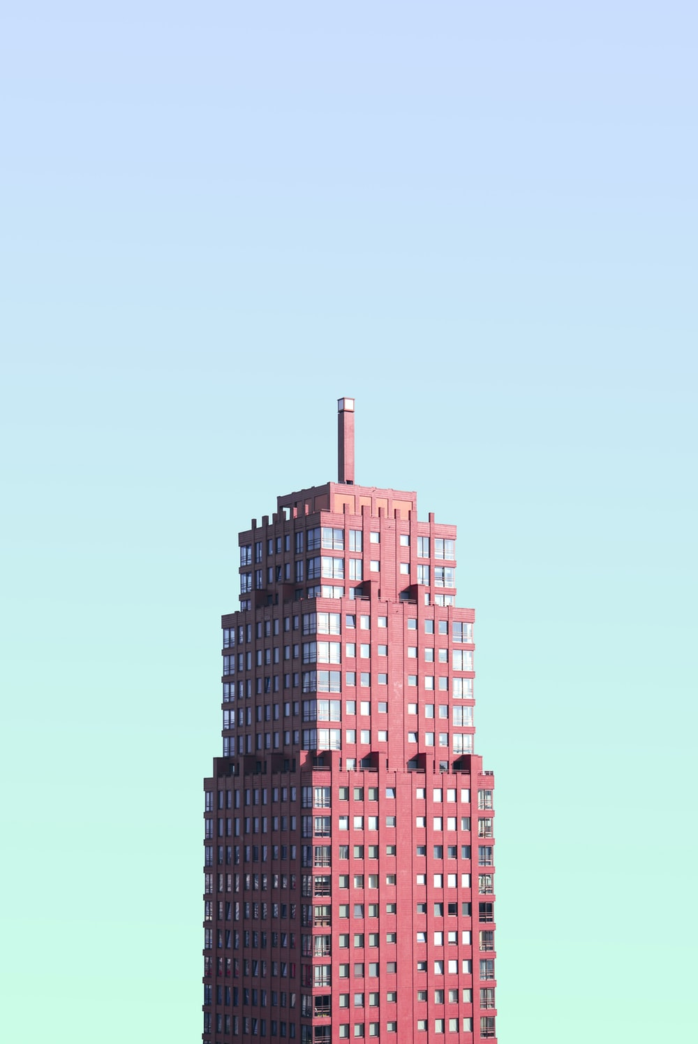 red high-rise building under blue sky