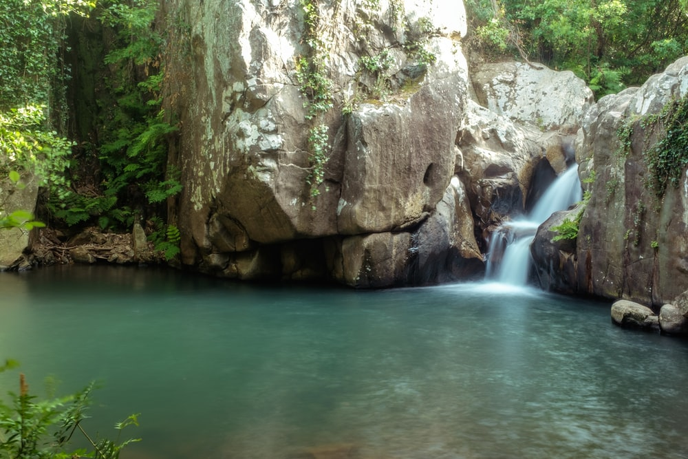 brown rock formation near waterfalls