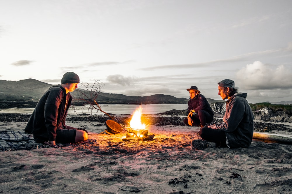three men in front of bonfire