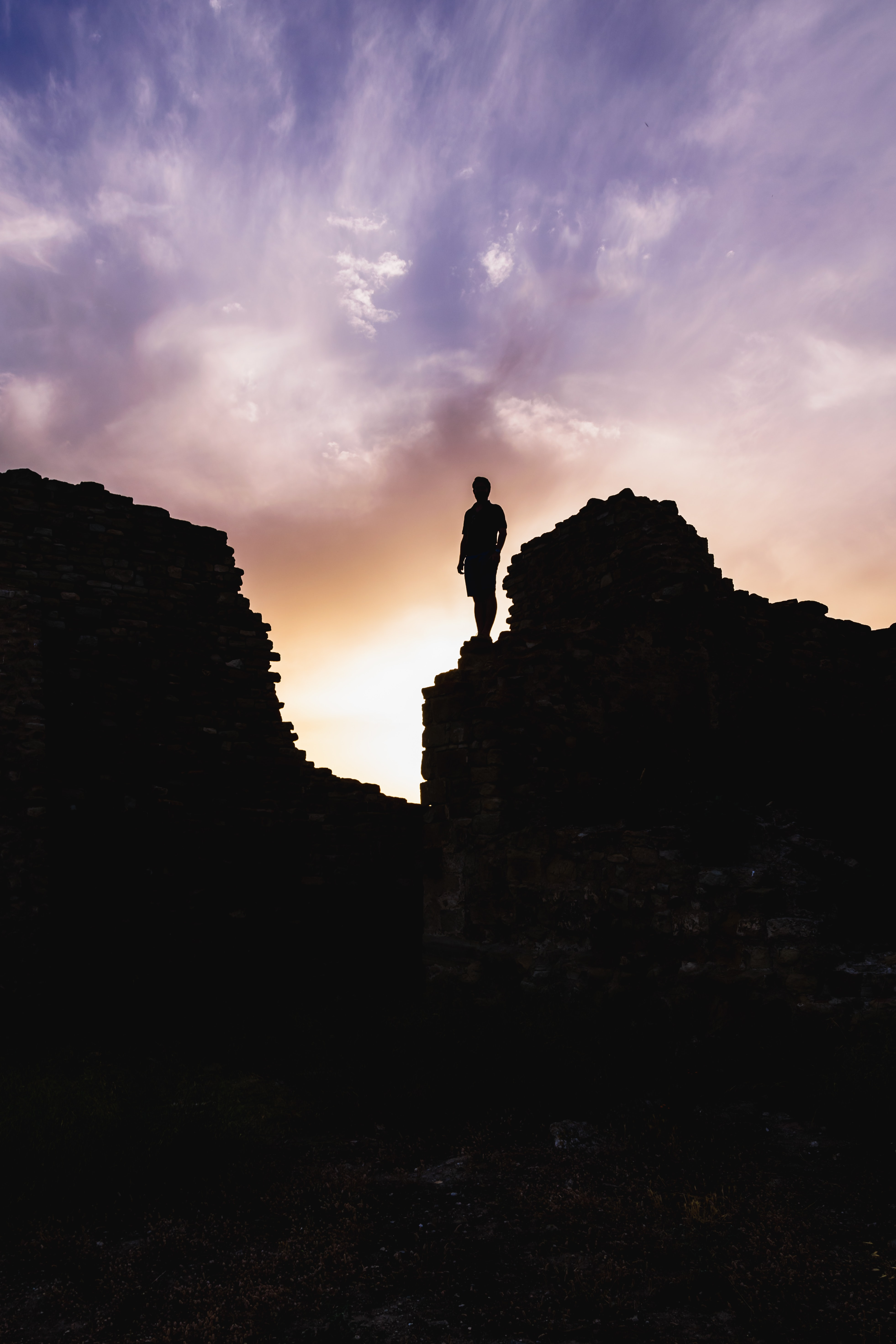 silhouette of man standing on rock formation