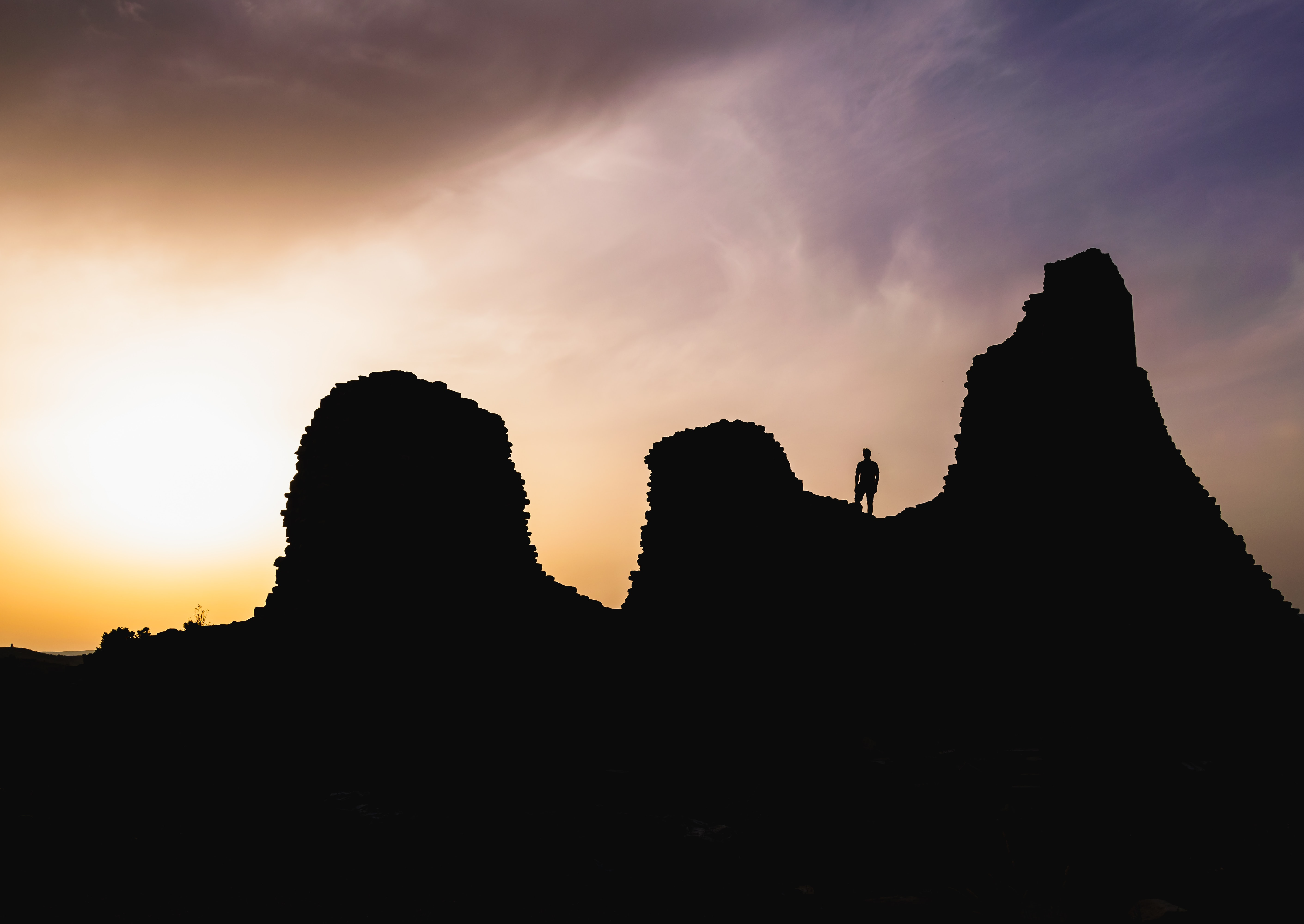 silhouette photography of person standing on cliff