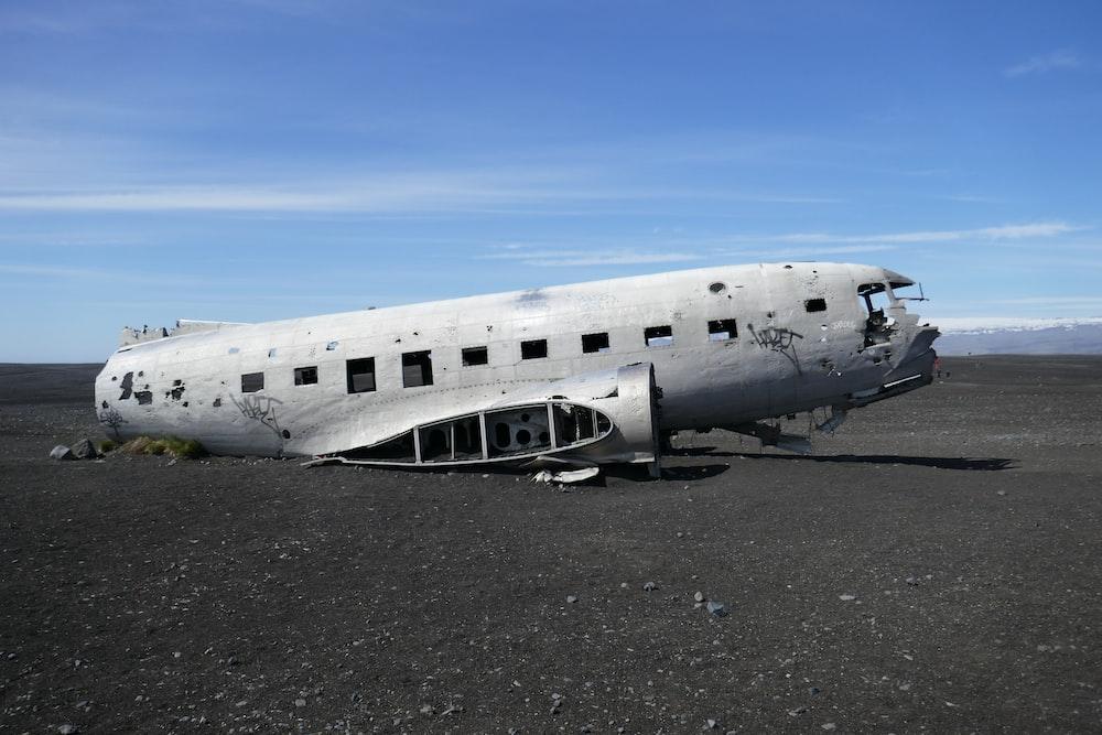 wrecked white plane on gray gravel