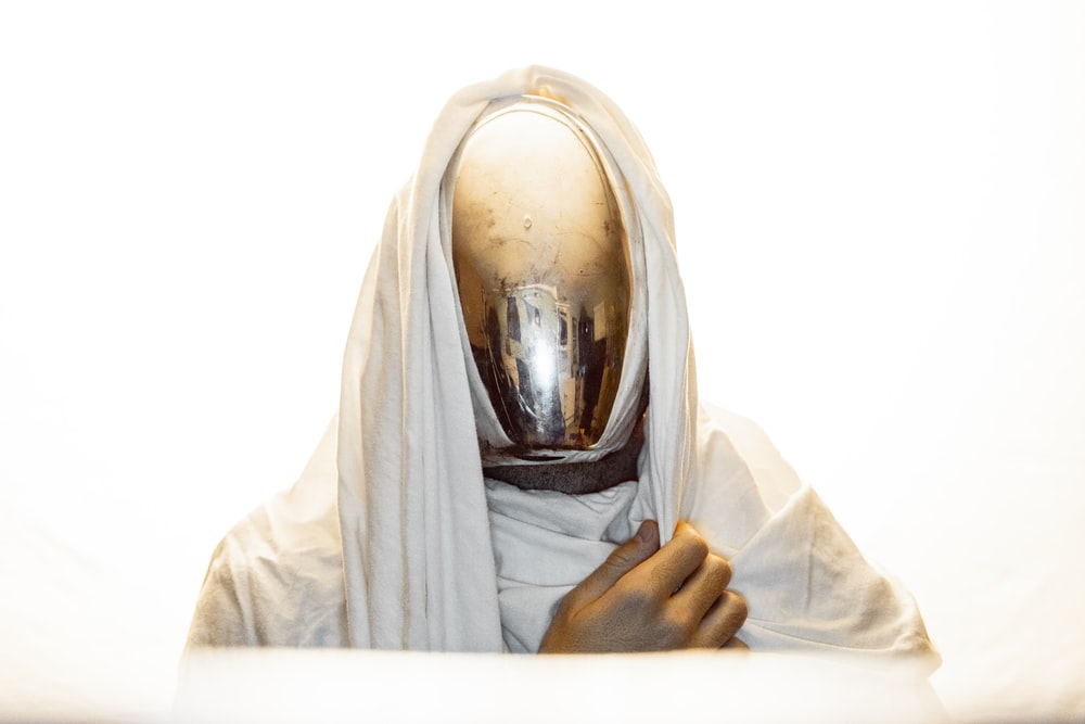 faceless character figure in white robe
