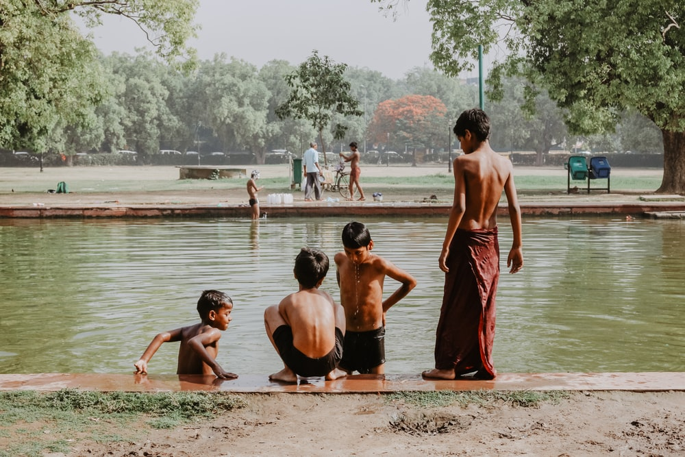 four toddlers standing near body of water
