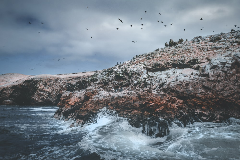 rock formation with sea waves photography