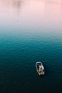 aerial photography of person sitting on boat on calm body of water